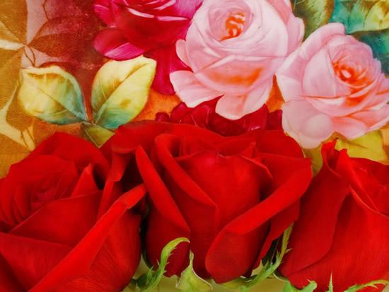 Rosas rojas reales sobre un fondo de rosas pintadas